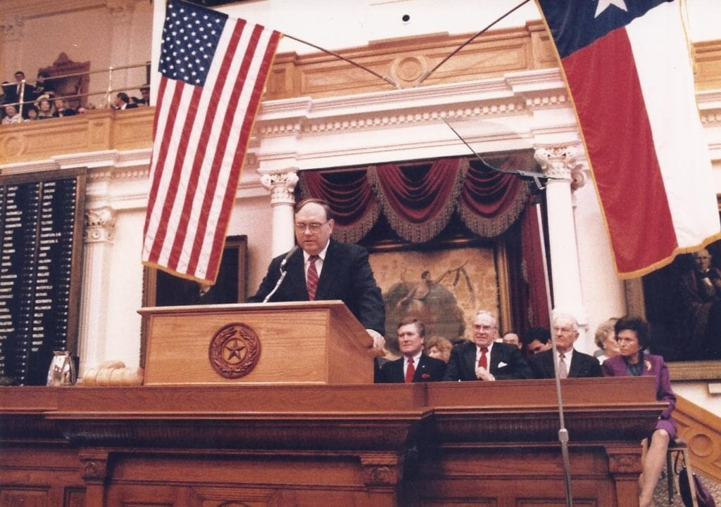 Featured: Rep. Lloyd Criss, D-Galveston, a longtime and former state lawmaker who helped champion the Labor movement, including helping secure rights for farm workers, addresses a joint session of the Texas Legislature in this image taken in the mid-1980s on the floor of the Texas House of Representatives. Also in this photograph, seated from left, are: Texas Speaker of the House Gib Lewis, D-Ft. Worth; U.S. Speaker of the House Jim Wright, D-Ft. Worth; Gov. Bill Clements; and Rita Clements, who served as a member of the University of Texas System Board of Regents. Criss passed away on Sunday, May 10, 2020.