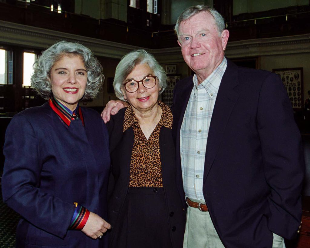 """FEATURED, FROM LEFT: In this image from 1997 taken on the floor of the Senate Chamber in the Texas Capitol, Sen. Judith Zaffirini, D-Laredo/Starr County, poses with Edith Royal and her husband, legendary University of Texas Longhorns head coach Darrell Royal, during a rehearsal for her Governor for a Day Celebration. """"I vividly recall him saying, 'I know one thing for sure: her blood runs burnt orange.' Indeed. Hook 'em, Horns!"""" said Zaffirini, who has a Bachelor of Science (B.S), a Master's of Arts (M.A.), and a Doctor of Philosophy (Ph.D.) from the University of Texas at Austin."""